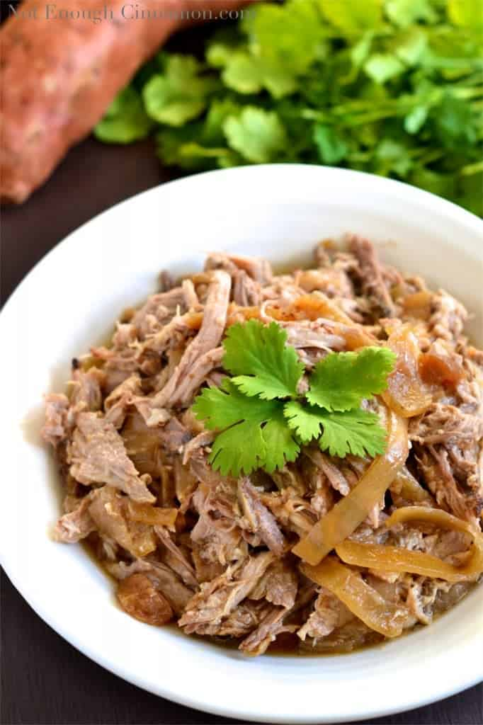 Slow Cooker Pulled Pork with Apples and Onions served in a white bowl with a fresh cilantro leave on top