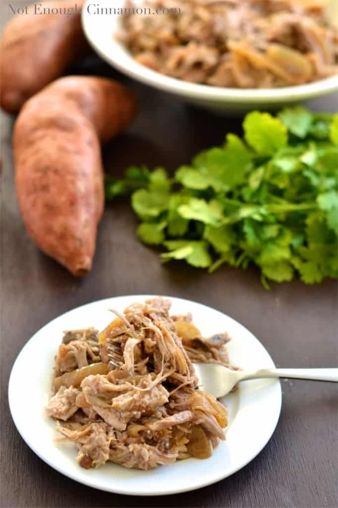 a serving of Slow Cooker Pulled Pork with Apples and Onions served on a small white plate with sweet potatoes and cilantro in the background