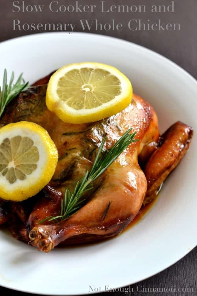 crispy Slow Cooker Whole Chicken topped with lemon slices and rosemary sprigs served in a big white dish