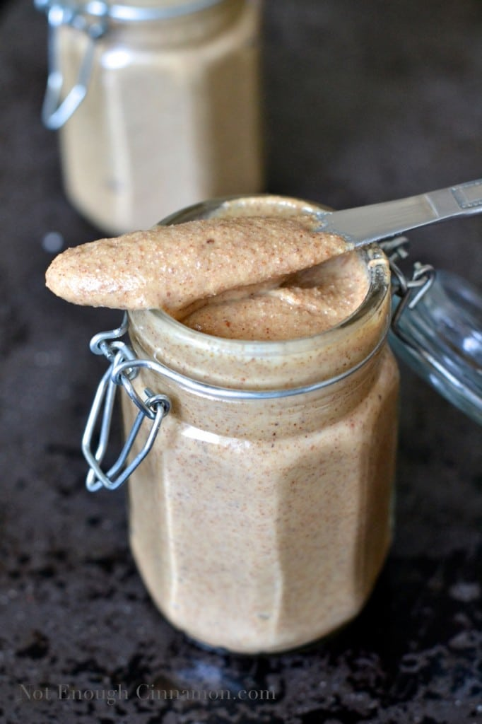 a knife freshly dipped into homemade almond butter resting on a jar of almond butter