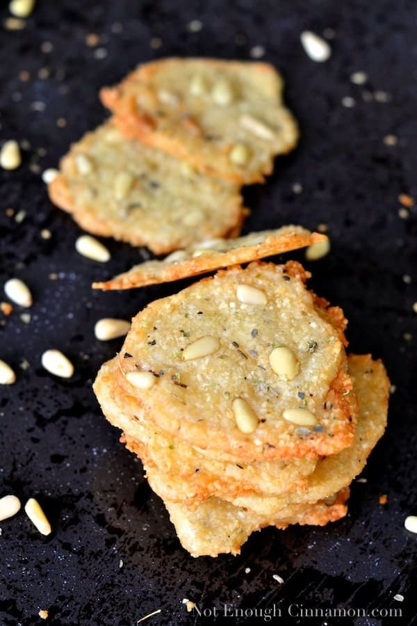 Crisp Parmesan Chips with Oregano and Pine Nut whimsically scattered on a black surface