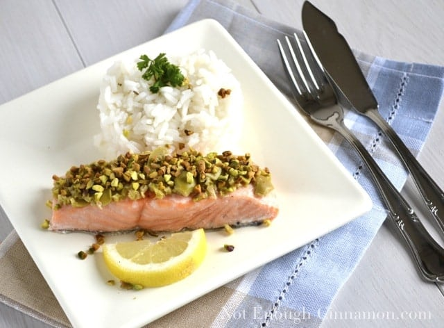 Salmon with Green Olive and Pistachio Topping served on a white plate