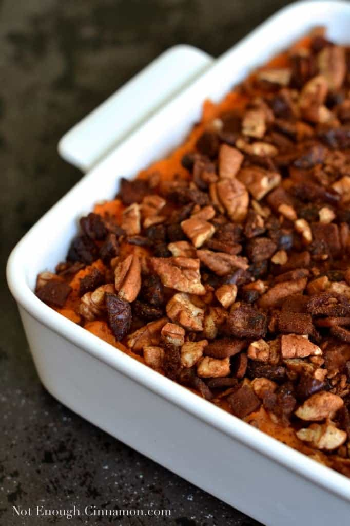 Sweet Potato Casserole with Pecans, Cranberries and Bacon sprinkled on top, served in a white casserole dish