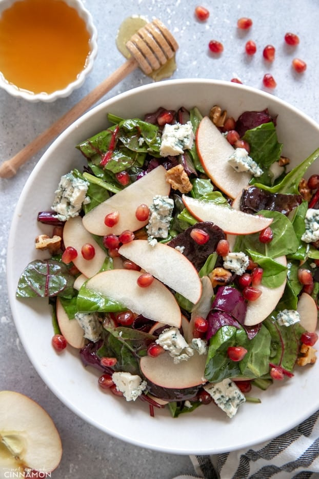 Apple and blue cheese salad in a white plate with pomegranate arils and honey on the side