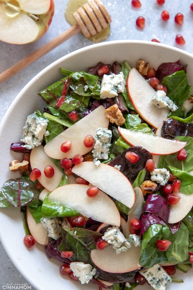 Apple and blue cheese salad with a sliced apple and honey dipper on the side