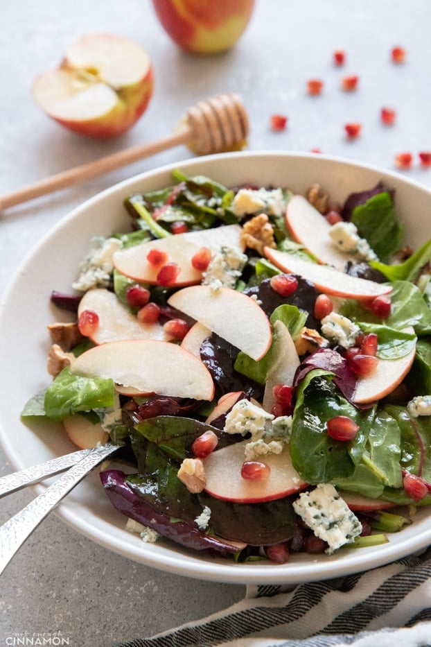 Apple and blue cheese salad in a large salad plate with a serving spoon and fork