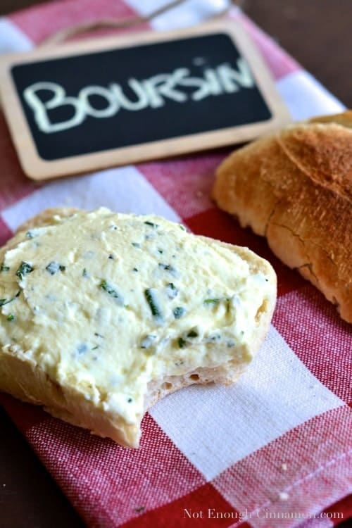 Homemade Boursin Cheese spread onto a slice of baguette with one bite taken out the front