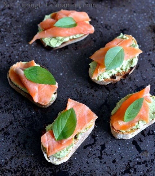 Smoked Trout and Basil Pesto Cream Cheese Crostini topped with fresh basil leaves and arranged on a black surface