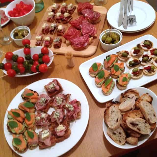 a display of different crostini and bite-sized appetizers on a table