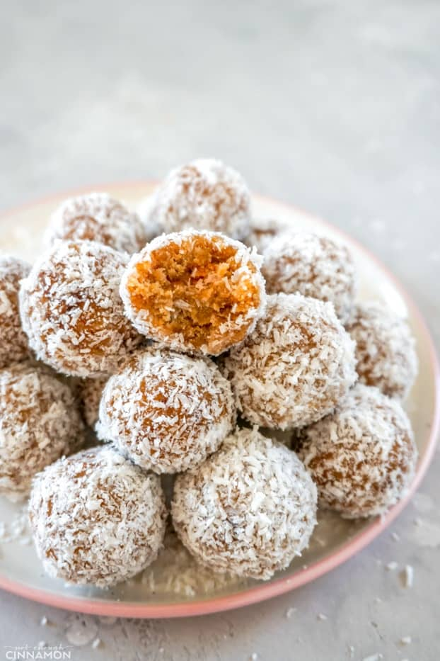 A pile of paleo energy bites on a white and pink plate, on a grey background