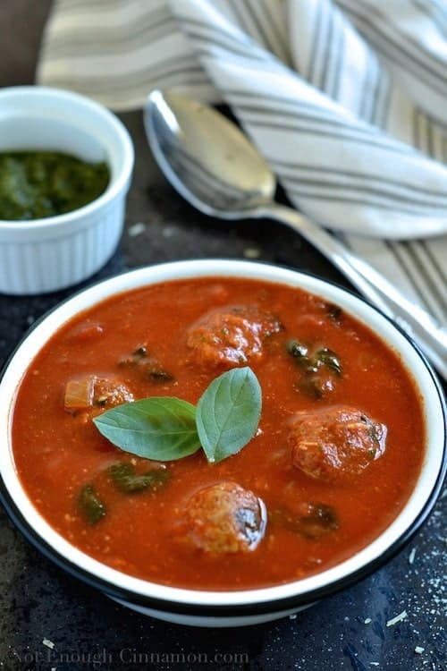 a bowl of Italian Meatball Soup with a rich tomato base sprinkled with fresh basil leaves