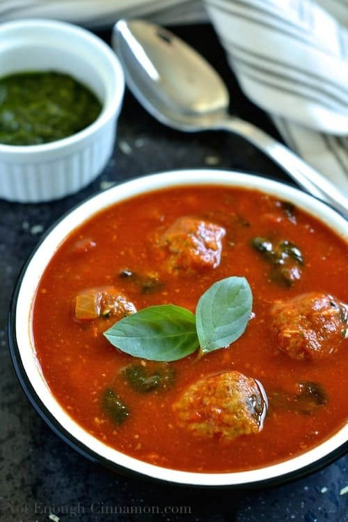 close-up of a bowl of Italian Meatball Soup with a rich tomato base sprinkled with fresh basil leaves