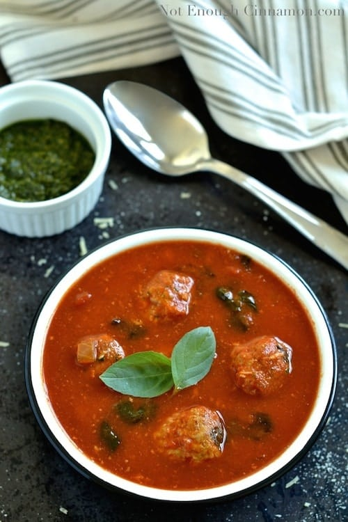 overhead shot of a bowl of Italian Meatball Soup sprinkled with fresh basil leaves with a small dish filled with basil pesto in the background