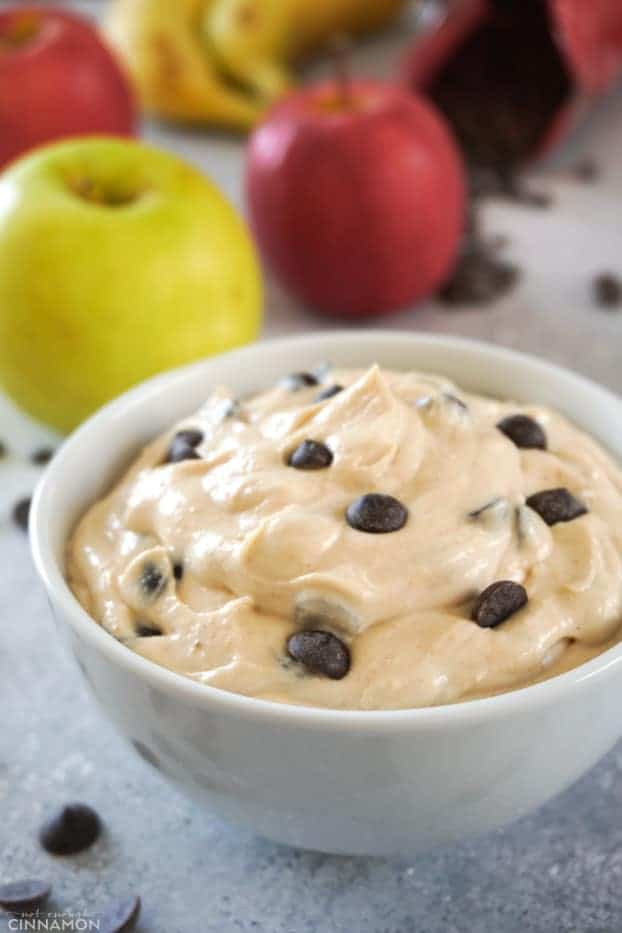 A white bowl of fruit dip with peanut butter and chocolate chips, with apples in the background.