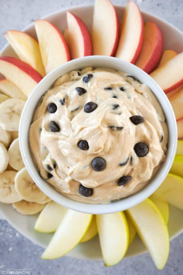 A small bowl of peanut butter chocolate chips fruit dips over a plate a cut fruits