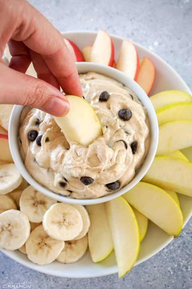 Apple dipped into peanut butter chocolate chips fruit dip in a white bowl, over a plate of fruit.