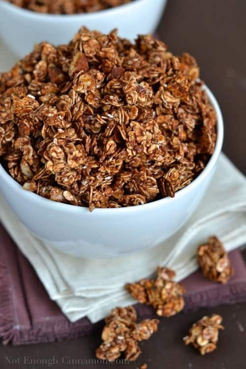 Quick and Easy Chocolate Granola with sweetened condensed milk piled up in a white cup