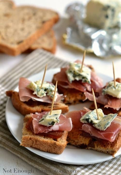Spanish Quince, Prosciutto and Blue Cheese Pintxos served on a white plate held together with toothpicks