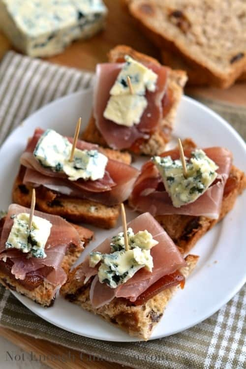 Quince, Prosciutto and Blue Cheese Pintxos served on a white plate with toothpicks holding them together