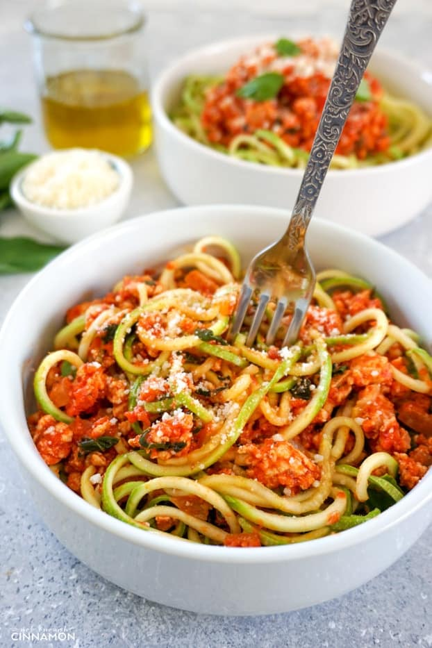A bowl of turkey bolognese with zucchini pasta with a fork about to dig in.