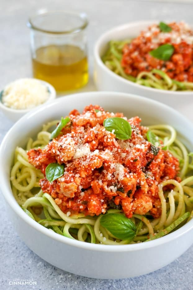Two bowl of turkey bolognese sauce over zucchini pasta, sprinkled with grated parmesan, in two shallow round plates