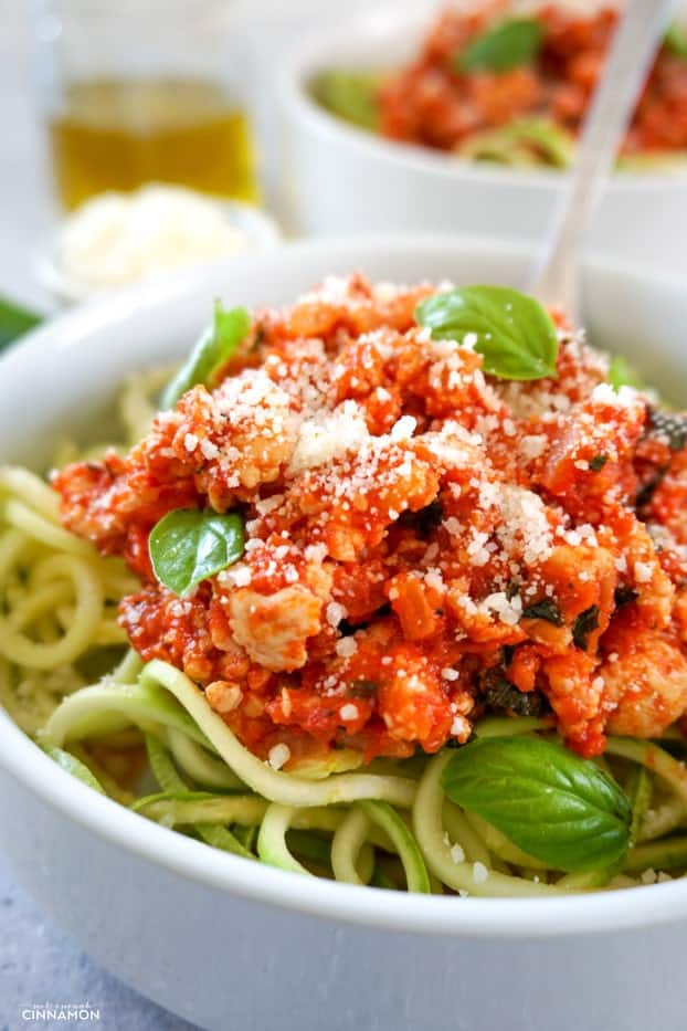 Close up on turkey bolognese sauce over zucchini pasta with fresh parmesan on top and a few fresh basil leaves