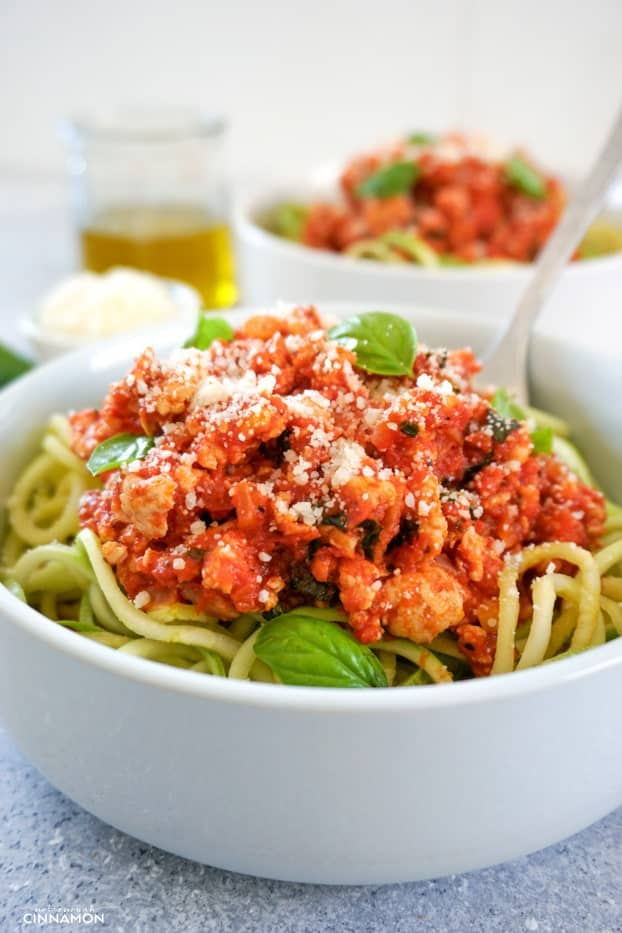 Turkey bolognese sauce on top of zucchini noodles in a white bowl, with olive oil and another bowl in the background.