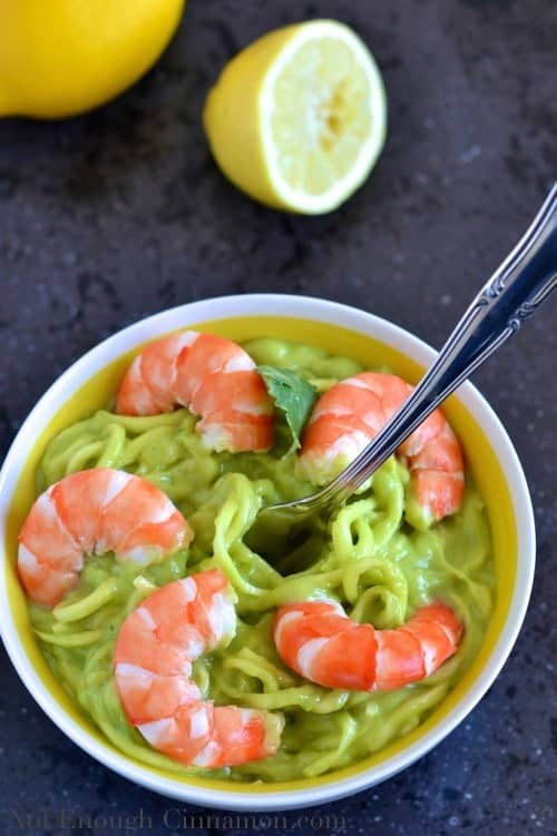 a fork twirling zucchini pasta with creamy avocado sauce and shrimps in a small white bowl
