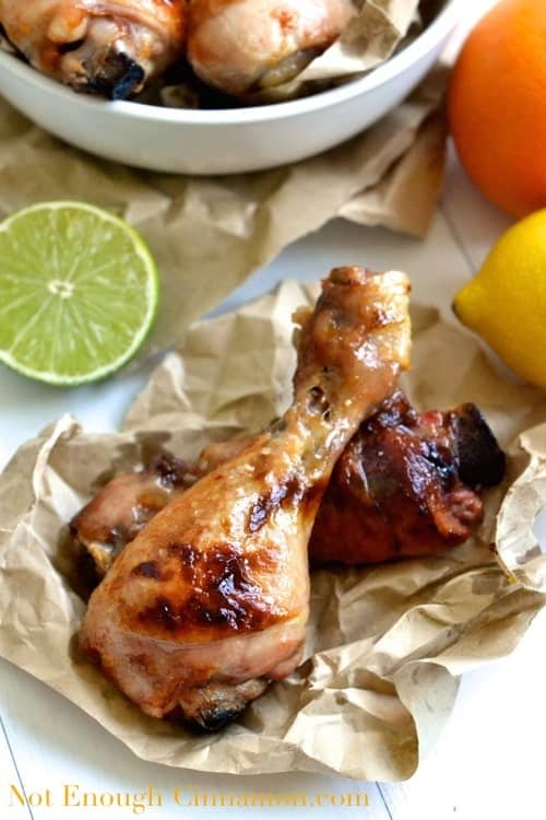 two Citrus Marinated Chicken Drumsticks served on a crinkled piece of parchment paper with some citrus fruit in the background