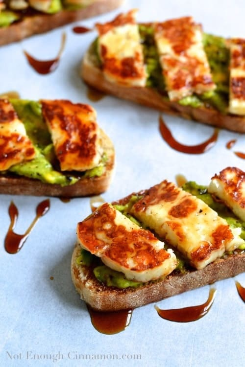 Tartine topped with Grilled Halloumi and mashed Avocado and drizzled with  Pomegranate Molasses - arranged on parchment paper