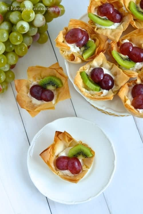 overhead shot of Ricotta Phyllo Cups decorated with grapes and kiwi slices on a cake stand and a white plate - phyllo cups recipe