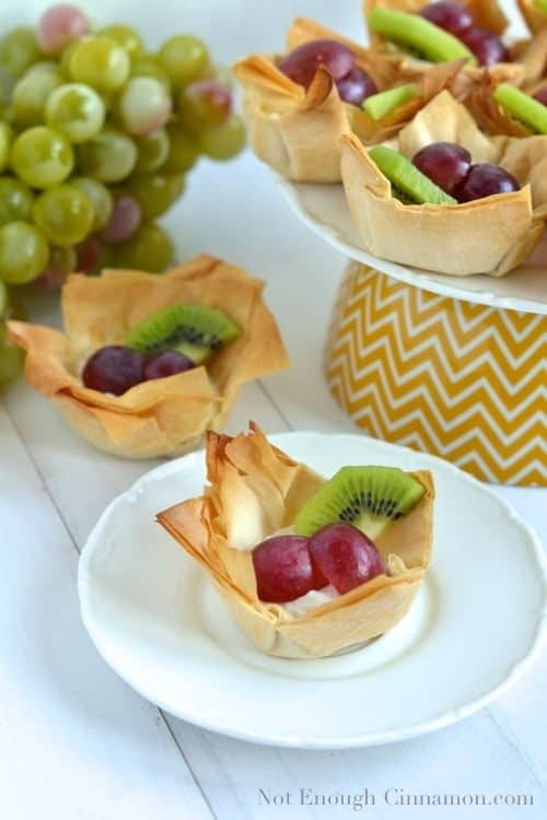 Dessert Phyllo Cups filled with ricotta, grapes and kiwi slices arranged on a cake stand and a single white plate- phyllo cups recipe