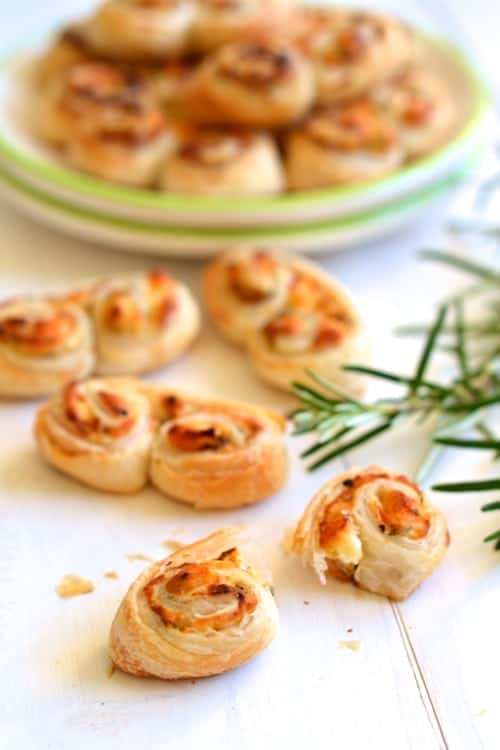 Goat Cheese, Mustard and Rosemary Palmiers arranged on a table with a plate of palmiers in the background - palmiers recipe