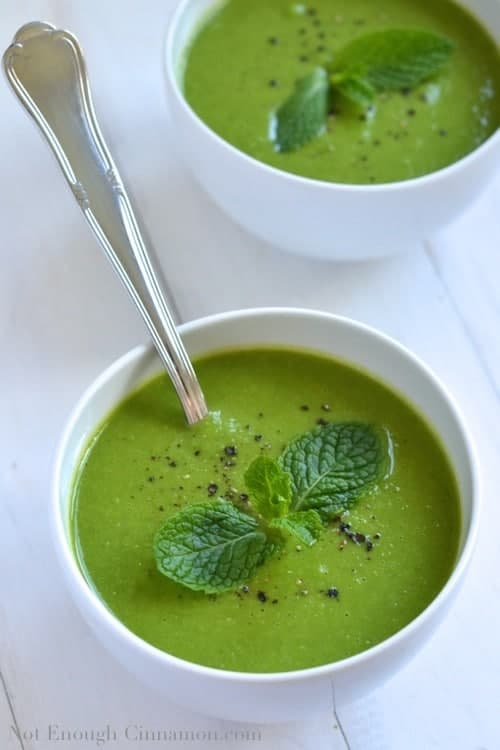 overhead shot of Pea and Mint Soup in a white bowl served with a spoon