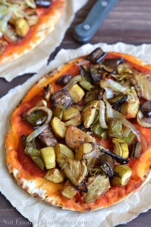 homemade gourmet pizza with roasted vegetable pizza toppings on a piece of parchment paper