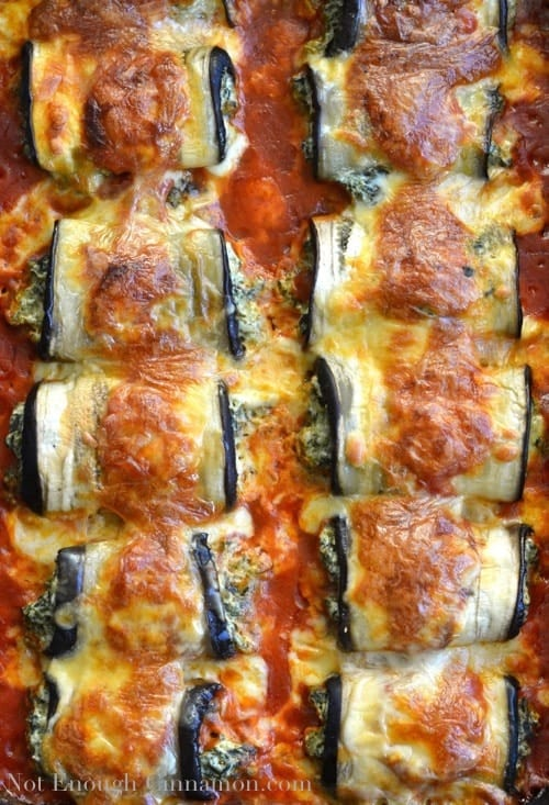 overhead of a casserole dish with baked eggplant rollatini stuffed with cheese and spinach and bathed in a thick Italian tomato sauce