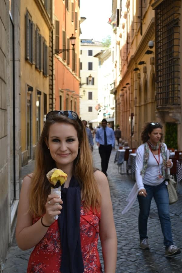 a woman holding an ice cream cone in the streets of Rome