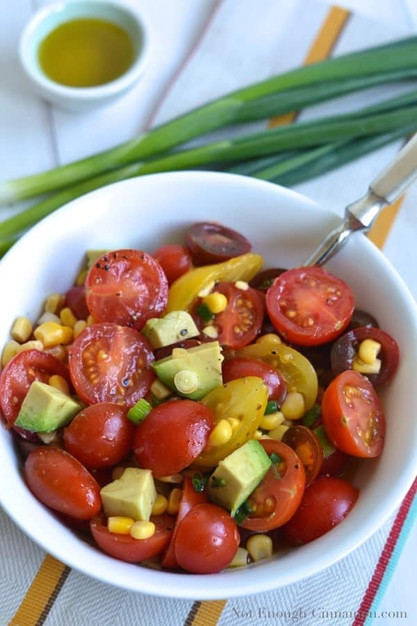 overhead shot of Tomato, Corn and Avocado Salad in a white bowl with some scallions and a little dish with dressing in the background