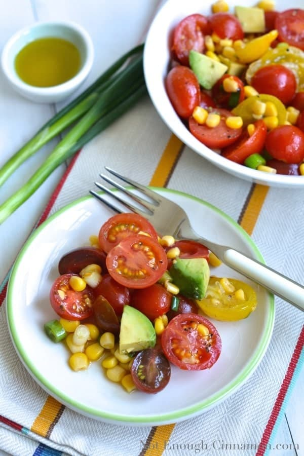 two small bowls of Corn Tomato Avocado Salad with some spring onions and a small dish with dressing on the side