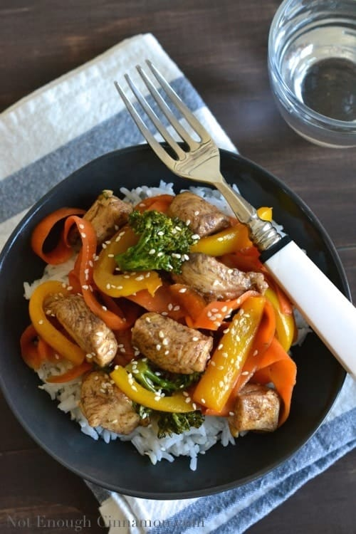 5-Spice Chicken & Vegetable Stir-Fry with homemade chicken stir-fry sauce served over jasmine rice on a black plate