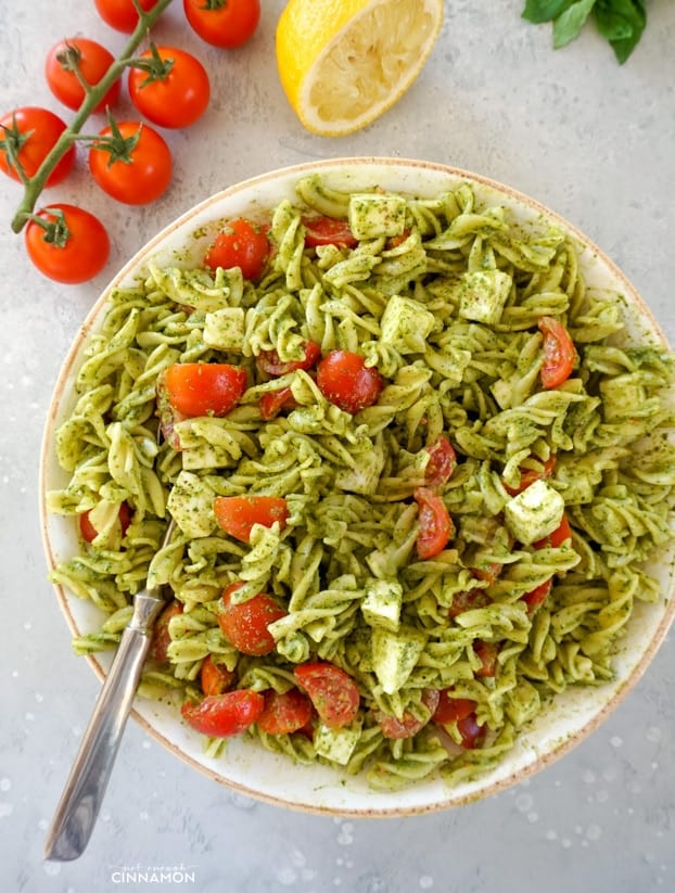 Fusilli pasta, cherry tomatoes, mozzarella with a pesto dressing in a large white bowl, with a large spoon, tomatoes and half a lemon in the background.