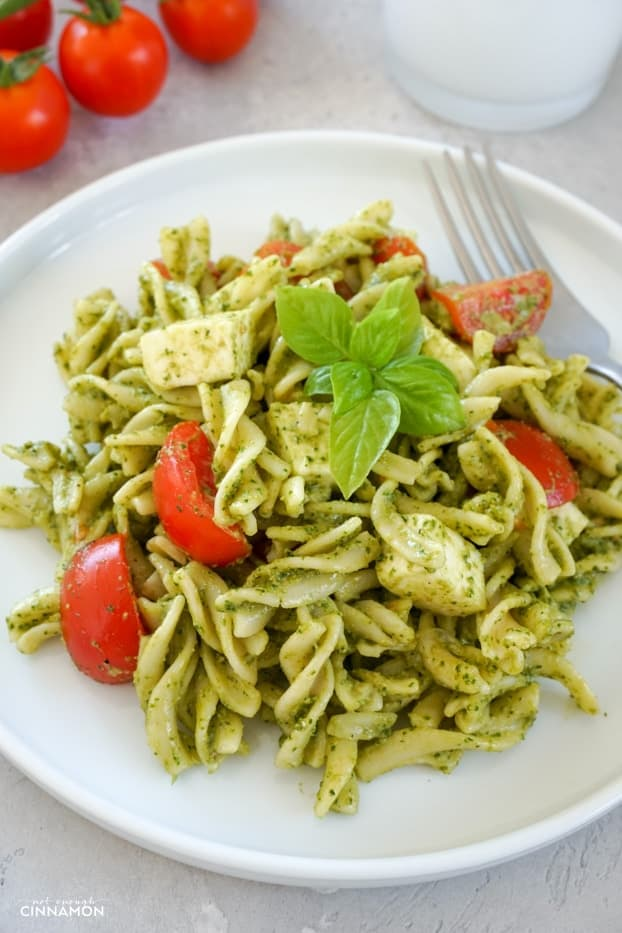 Fusilli pasta, cherry tomatoes, mozzarella with a pesto dressing in a small white plate, with a fork on the side, a white glass and tomatoes in the background.