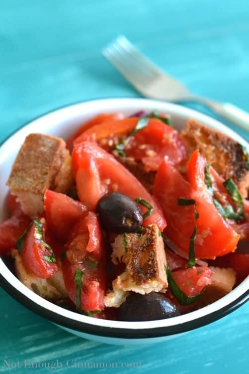 close-up of a bowl of easy panzanella salad with black olives, tomatoes and capers