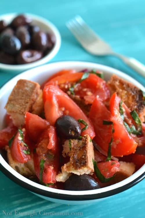 Easy Panzanella Salad with black olives and tomatoes served in a white bowl