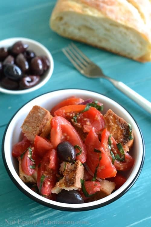 a small bowl with panzanella salad with some sourdough bread and black olives in the background