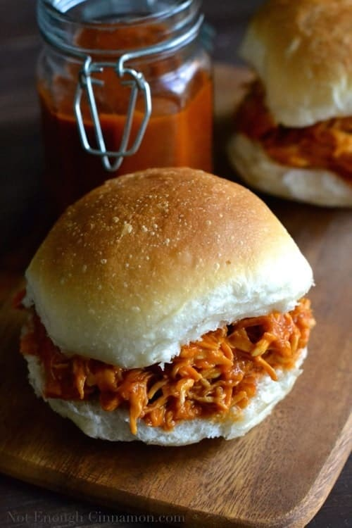 Healthy Peach BBQ Pulled Chicken with homemade peach bbq sauce served in a burger bun with a jar of peach sauce in the background