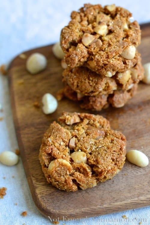 crunchy Paleo Macadamia Cookies arranged on a wooden board surrounded by macadamia nuts (paleo cookies recipe)