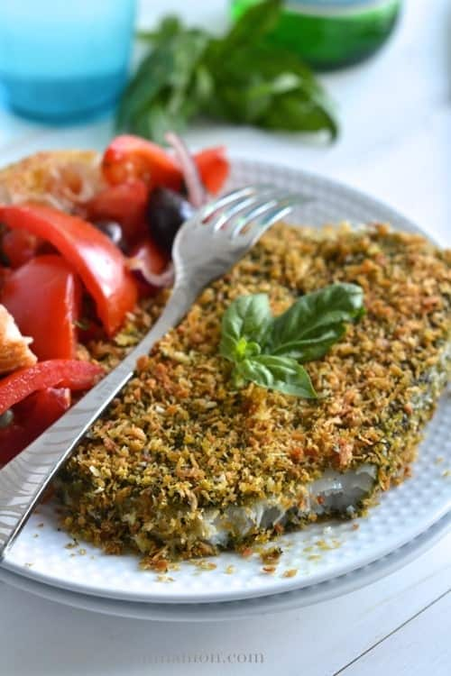 Pesto Panko Crusted Fish with one bite taken out the front, served with a side of panzanella salad