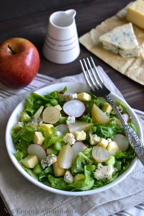 Ploughman's salad with apples, celery, radishes, cheddar and stilton served in a white bowl with salad ingredients in the background