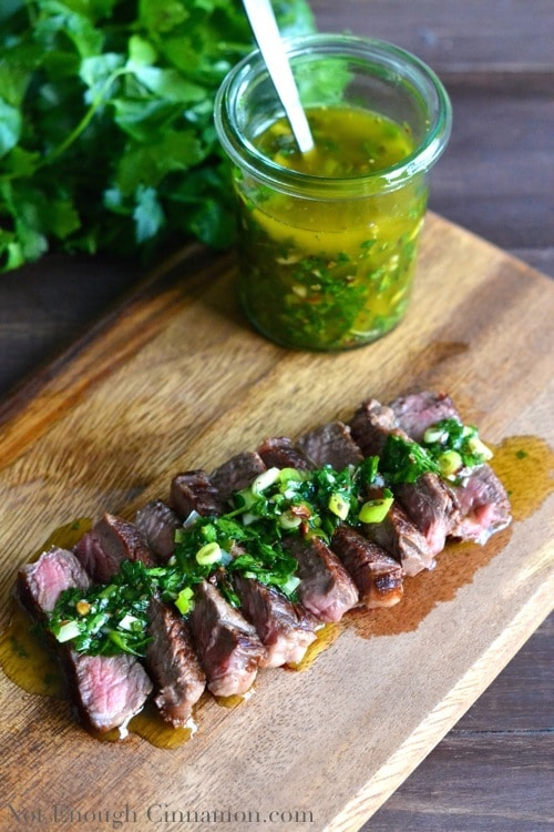 Juicy sliced of sirloin Steak with Chimichurri Sauce served on a wooden chopping board with a small dish of homemade chimichurri sauce in the background
